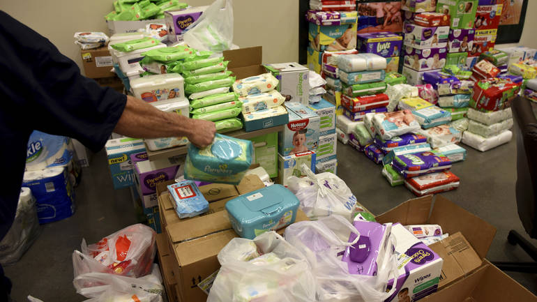 Diapers, wipes and other items are stacked as donations arrive for residents, displaced by the mandatory evacuations caused by the wildfires, gather at Rocky Top Sport World on US321 just outside of Gatlinburg, Tenn., Wednesday, Nov. 30, 2016. (Michael Patrick/Knoxville News Sentinel via AP)